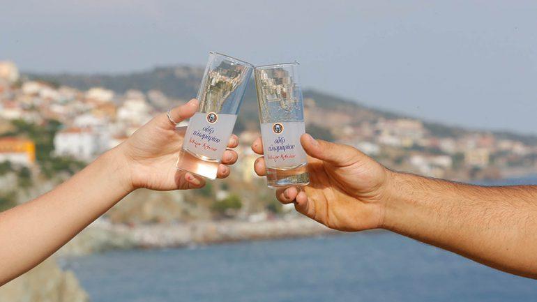 clinking glasses of ouzo plomari